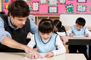 白人の先生と授業を受ける小学生の写真素材 [FYI02037264]