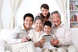 タブレットPCを見る家族の写真素材 [FYI02037482]