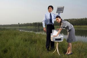 ソーラーパワーで印刷をするビジネスピープルの写真素材 [FYI02037551]