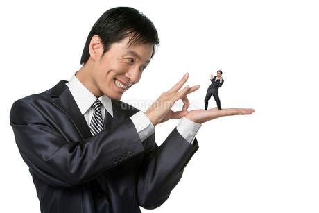 手の上に乗ったスーツ姿の小人をはじこうとするビジネスマンの写真素材 [FYI02037558]
