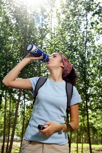 林の中でドリンクを飲む若い女性の写真素材 [FYI02037607]