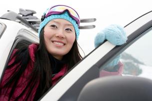 車から降りるスキーウェアを着た若い女性の写真素材 [FYI02037636]