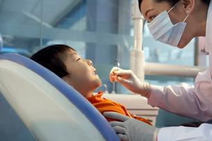 歯の治療をする歯医者と少年の写真素材 [FYI02037767]
