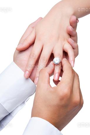 女性の指に婚約指輪をはめる男性の手の写真素材 [FYI02038175]