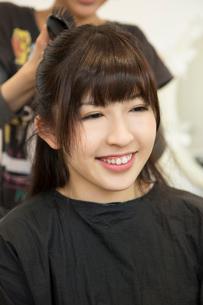 髪をセットしてもらう女性の写真素材 [FYI02038543]