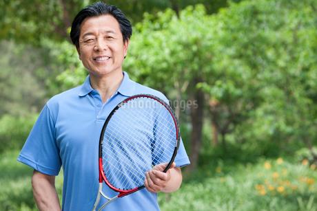 テニスラケットを持った熟年男性の写真素材 [FYI02038805]