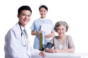 シニア女性の血圧を測る医師と看護師の写真素材 [FYI02039059]