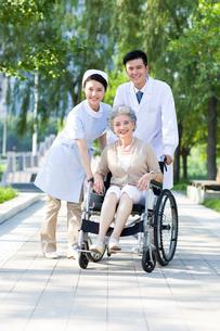 車椅子に乗った女性と医師と看護婦の写真素材 [FYI02039223]