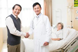 入院中の妻を見舞う男性と医師の写真素材 [FYI02039244]