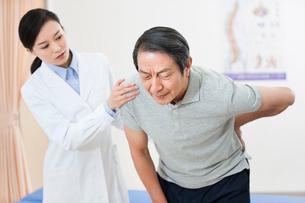 腰を抑える男性と女医の写真素材 [FYI02039644]