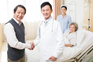 入院中の妻を見舞う男性と医師の写真素材 [FYI02039985]
