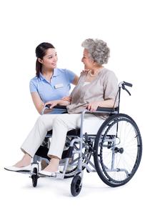 車いすに乗る女性と介護士の写真素材 [FYI02040126]