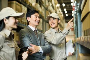 倉庫で働くビジネスマンと作業員の写真素材 [FYI02040943]