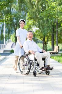 車椅子に乗った男性と看護婦の写真素材 [FYI02040983]