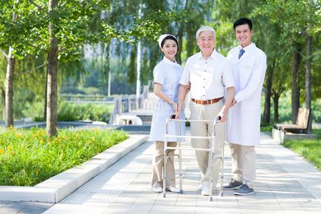歩行器を持って歩く男性と医師と看護婦の写真素材 [FYI02041071]