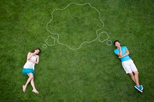 芝生の上に寝転ぶ若いカップルの写真素材 [FYI02041583]
