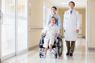 車椅子の女性を押す看護師と医者の写真素材 [FYI02041670]