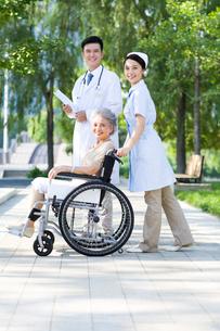 車椅子に乗った女性と医師と看護婦の写真素材 [FYI02041705]