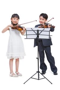 バイオリンを弾く少年少女の写真素材 [FYI02041811]