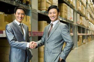 倉庫で握手をするビジネスマンの写真素材 [FYI02042109]