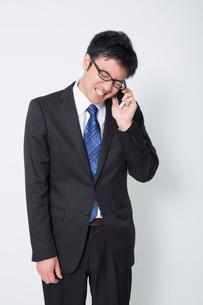携帯電話で謝罪するビジネスマンの写真素材 [FYI02042509]