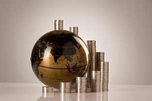 高く積まれた硬貨と地球儀の写真素材 [FYI02042518]