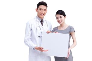 白紙のボードを持つ医師と女性の写真素材 [FYI02042720]