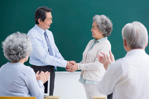 教授と握手をするシニア女性の写真素材 [FYI02042737]