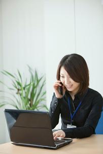 パソコンを見ながら携帯で話す女性の写真素材 [FYI02043492]