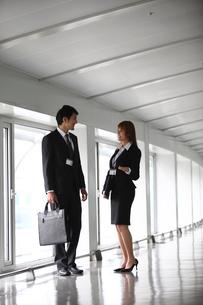 廊下で話すビジネスマンとビジネスウーマンの写真素材 [FYI02043571]