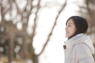 冬の木立と笑顔の女性横顔の写真素材 [FYI02044116]