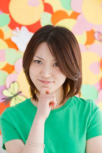 口元に手をあてる女性 カラフル背景の写真素材 [FYI02044150]