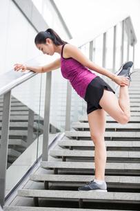 階段で脚のストレッチをする若い女性の写真素材 [FYI02045661]