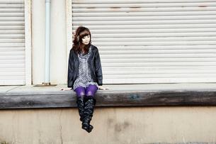 冬の屋外で腰掛ける女性の写真素材 [FYI02045767]