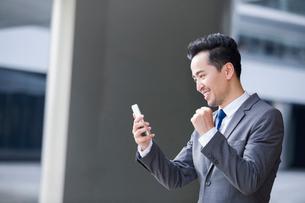興奮しながらスマートフォンを見ているビジネスマンの写真素材 [FYI02046163]