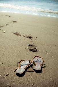 砂浜のサンダルと足跡の写真素材 [FYI02047571]