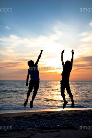 夕焼けの砂浜でジャンプする2人の若い男性の写真素材 [FYI02047577]
