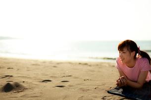 砂浜に寝転ぶ若い女性の写真素材 [FYI02047605]