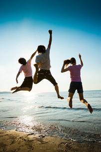 波打ち際でジャンプする若者たちの写真素材 [FYI02047667]