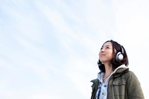 青空と音楽を聴く女性の写真素材 [FYI02047712]
