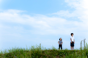 野原に立つ2人の子供と空の写真素材 [FYI02047828]