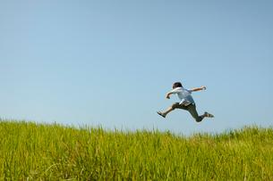 草原でジャンプする若い男性と青空の写真素材 [FYI02047839]