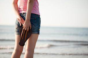 海辺でサンダルを持つ女性の写真素材 [FYI02048032]