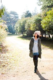公園を散歩する帽子を被った女性の写真素材 [FYI02048273]