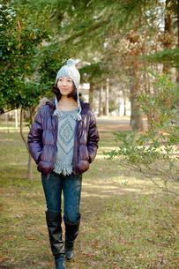 公園を散歩する毛糸の帽子とダウンジャケットを着た女性の写真素材 [FYI02048283]