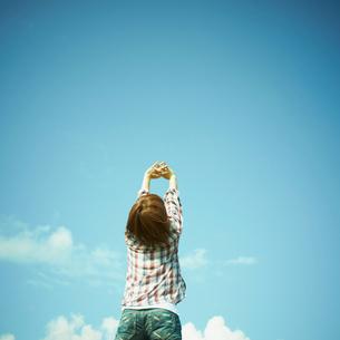 伸びをする女性と青空の写真素材 [FYI02048300]
