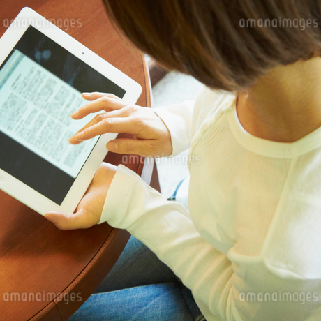 タブレットPCを操作する女性の写真素材 [FYI02048438]