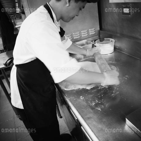 ピザの生地を伸ばす店員の写真素材 [FYI02048624]