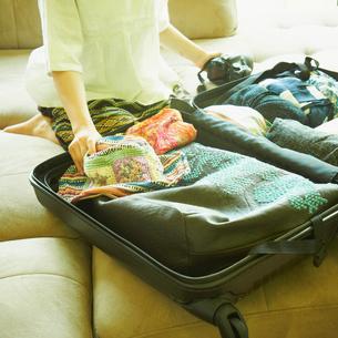 スーツケースに荷物を詰める女性の写真素材 [FYI02048630]