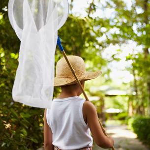 補虫網を持ち麦わら帽子を被った男の子の写真素材 [FYI02048631]